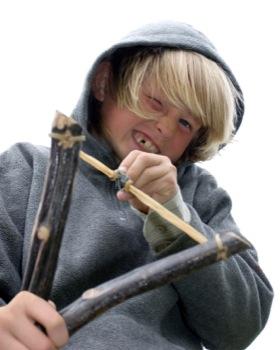 Niño apuntando con un tirachinas