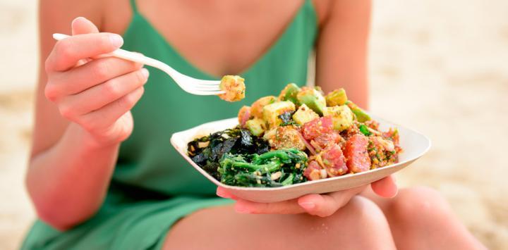 Una mujer flexitariana sostiene un plato de verduras