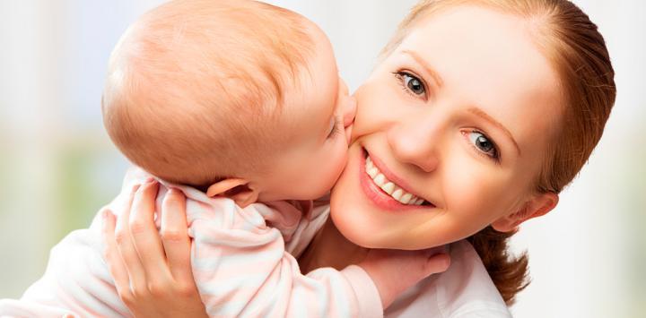 Un bebé besa a su madre mientras esta lo sostiene en brazos