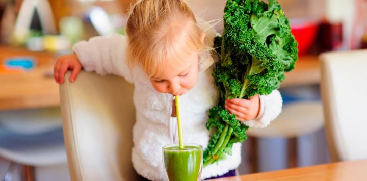 Una niña sujeta una col rizada en la mano mientras bebe un zumo de kale