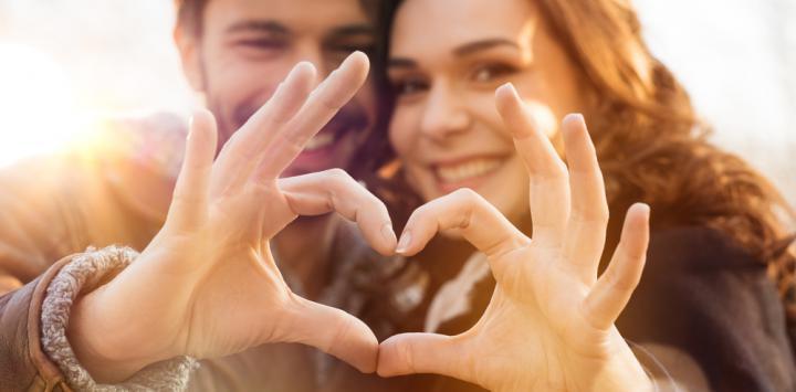 Pareja sonríe a la cámara formando con sus manos un corazón
