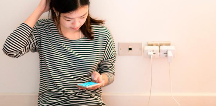 Una joven mira con preocupación el nivel de batería de su móvil