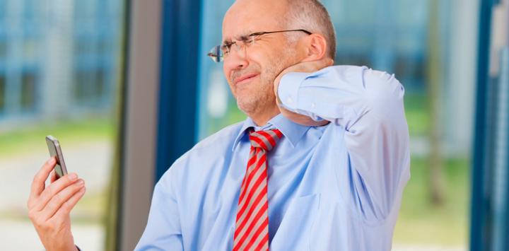 Un hombre con smartphone se duele de las cervicales