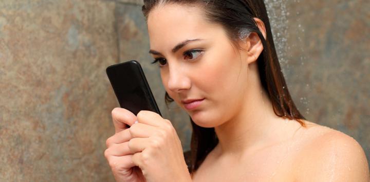 Una joven consulta su smartphone mientras se ducha