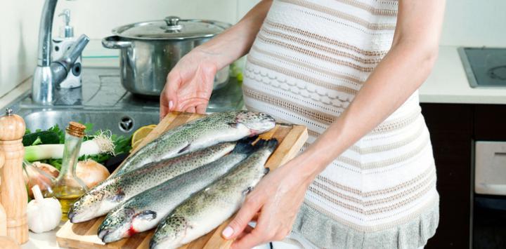 Embarazada preparando pescado para comer