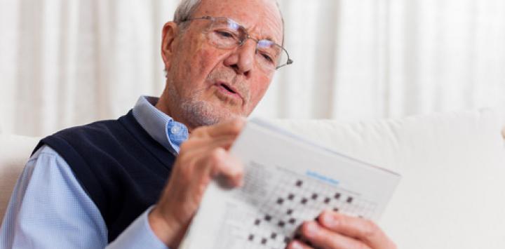 Un hombre mayor hace crucigramas