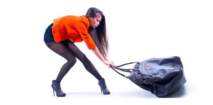 Una mujer se esfuerza en arrastrar un pesado bolso