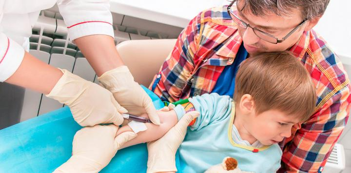 Doctor haciendo un análisis de sangre a un niño.