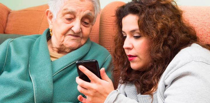 Una joven muestra la pantalla de un móvil a una anciana