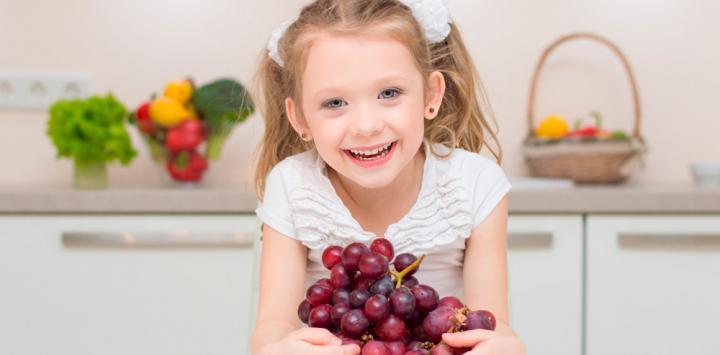 Niña comiendo uvas enteras