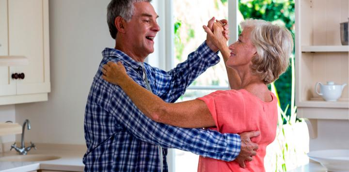 Una pareja de adultos mayores baila en la cocina de su casa