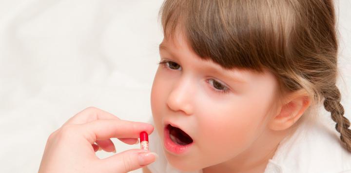 Niña pequeña tomando pastilla
