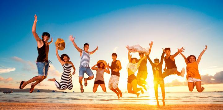 Jóvenes felices saltando en la playa