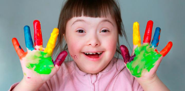 Niña con Síndrome de Down con las manos pintadas y feliz