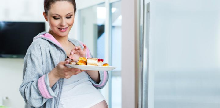 Mujer embarazada sale de la cocina con un plato de pasteles en la mano