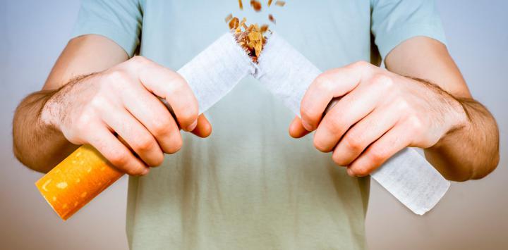 Hombre rompe un cigarrillo con las manos