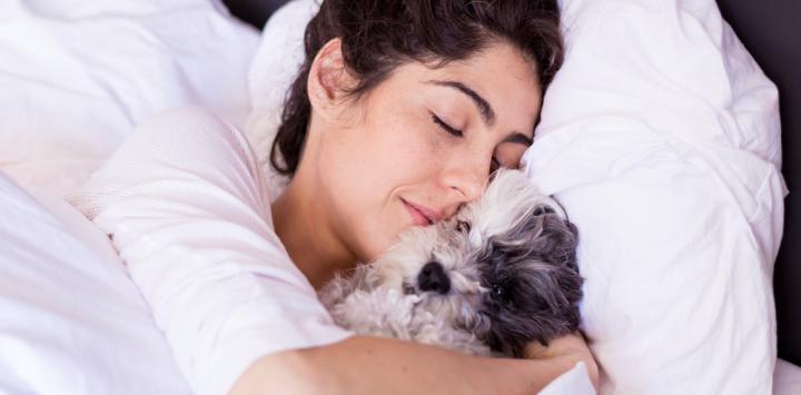 Mujer joven durmiendo con su perro