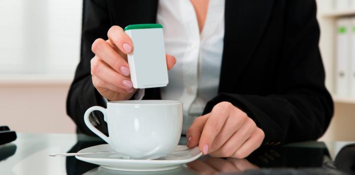 Mujer echando edulcorante en el café