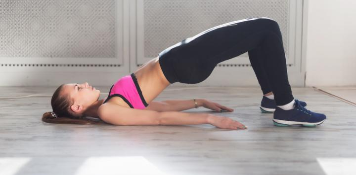 Una joven realiza un ejercicio que fortalece los músculos de la espalda