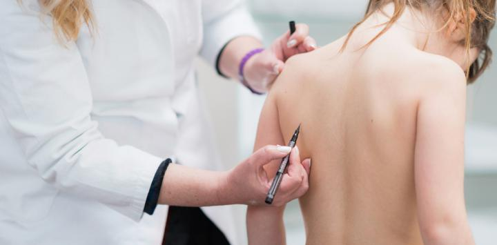 Una doctora examina la espalda de una niña