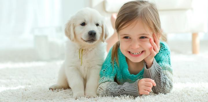 Niña sonríe en compañía de su mascota