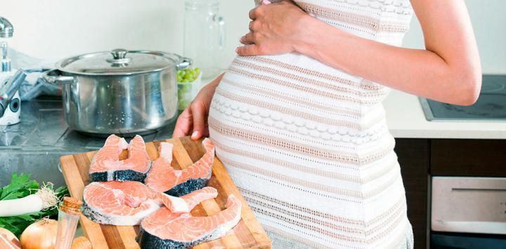 Mujer embarazada tomando salmón