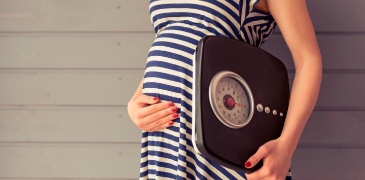 Embarazada con una báscula para medir su peso