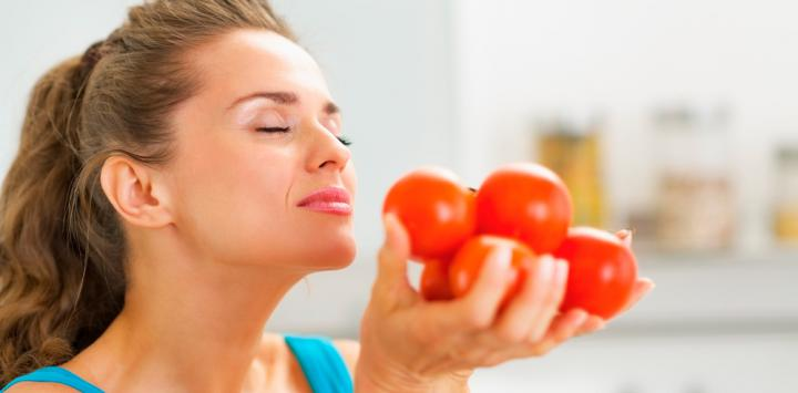 Una mujer aspira el aroma de tomates que sostiene en sus manos