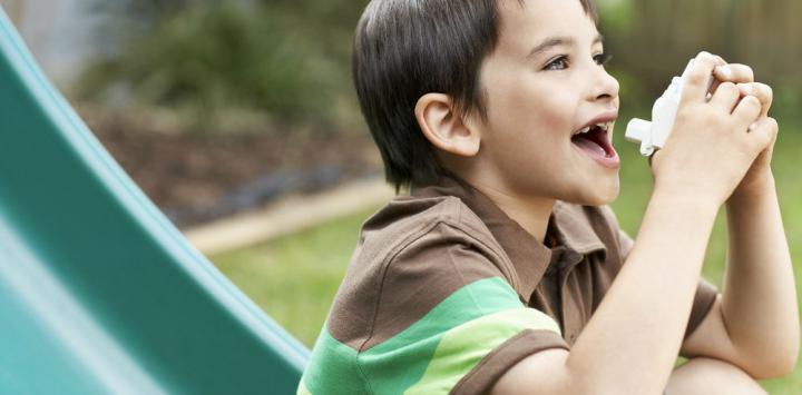 Niño con asma sentado en un tobogán, a punto de inhalar su medicación