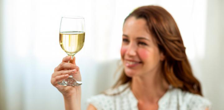 Mujer con rosácea levanta una copa de vino blanco