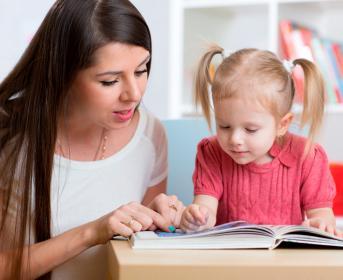 Madre enseñando a leer a su hija