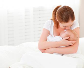 Madre acunando con el brazo izquierdo a su bebé
