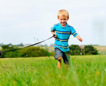 Niños corriendo al aire libre con su perro