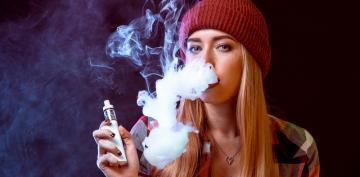 Adolescente vapeando con un cigarrillo electrónico