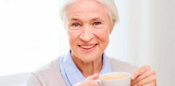 Una mujer ingiere una taza de café caliente