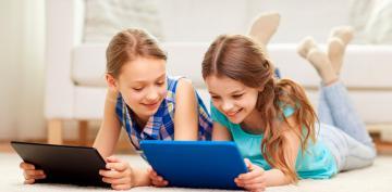 Niñas visualizando una tablet en casa