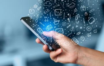 Una mano sujeta un smartphone del que 'brotan' símbolos de varios tipos de información