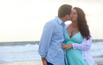 Una mujer embarazada besa a su pareja en una playa