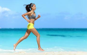 Una joven corre descalza por la playa