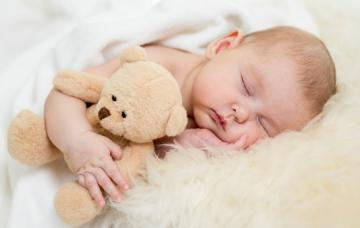 Bebé durmiendo con la mejilla apoyada en la mano y abrazando a su osito de peluche