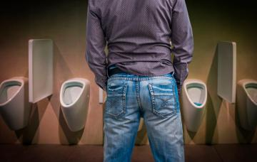Hombre orinando en un baño público