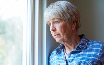Mujer mayor deprimida mirando por la ventana
