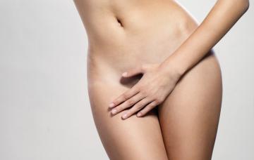 Mujer cubriendo sus genitales con la mano