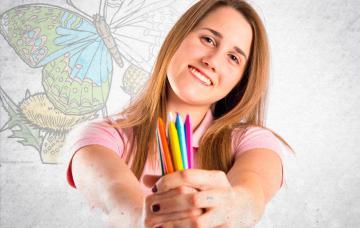 Una mujer muestra un puñado de pinturas de colores
