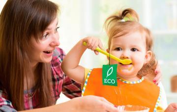 Una mama ofrece un alimento ecológico a su bebé