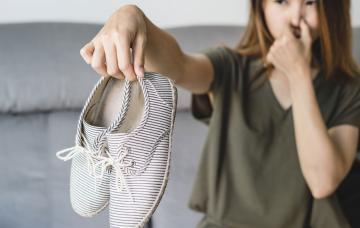 Mujer sujetando unas botas que desprenden mal olor