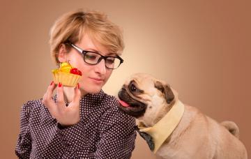 Un perro se inclina hacia un pastel que sostiene su dueña en la mano