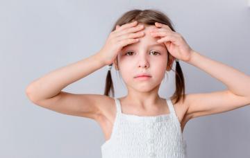 Una niña pálida se toca la frente