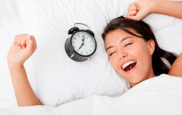 Una mujer se despereza en la cama por la mañana