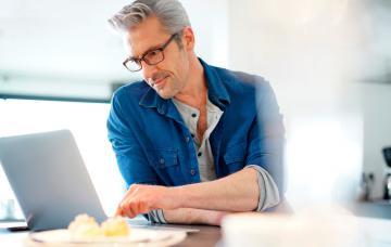 Hombre mira ofertas de trabajo en su portátil